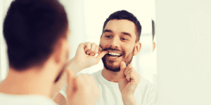 Reflection of Man Flossing in Mirror