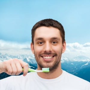 Man Holding Green Toothbrush Up to Face on Mountain Background